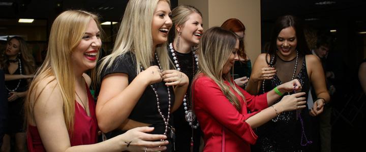 students smiling at mardi gras ball
