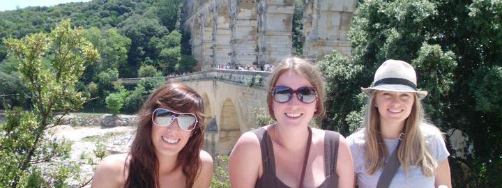 three students smiling at Pont du Gard