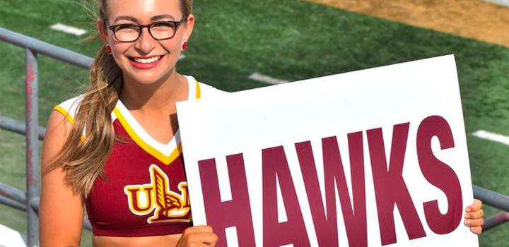 member holding a Hawks sign smiling