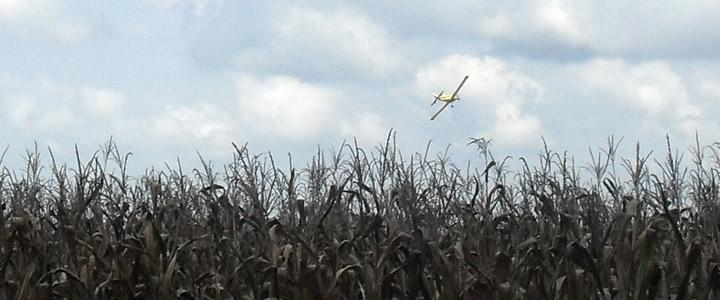photo of crop duster plane in sky over field