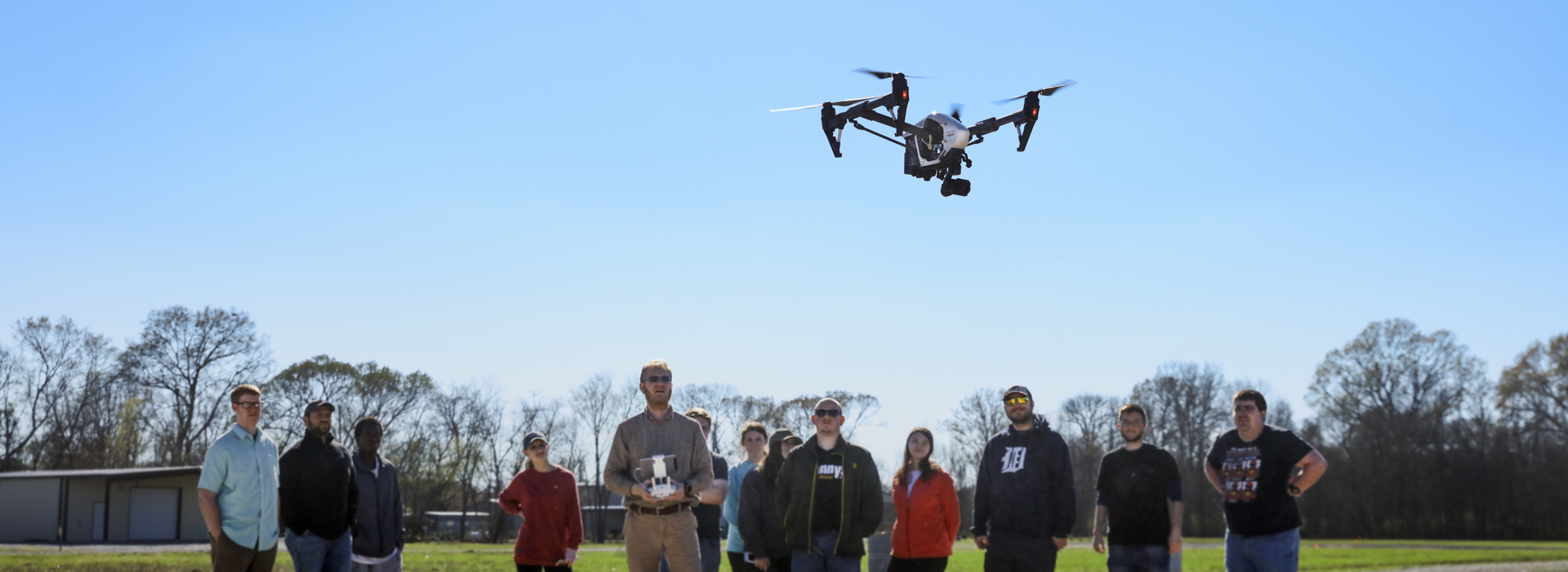 Students and professor watch a drone take flight